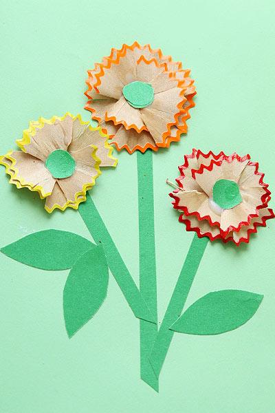 Приклейте стружку в виде цветочков. Сверху наклейте кружочки - серединки цветков
