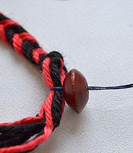 Проденьте в полученную петельку хвостик от косички и протяните его в отверстие бусинки