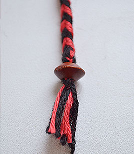 Завяжите под бусинкой два узелка и обрежьте лишние нитки