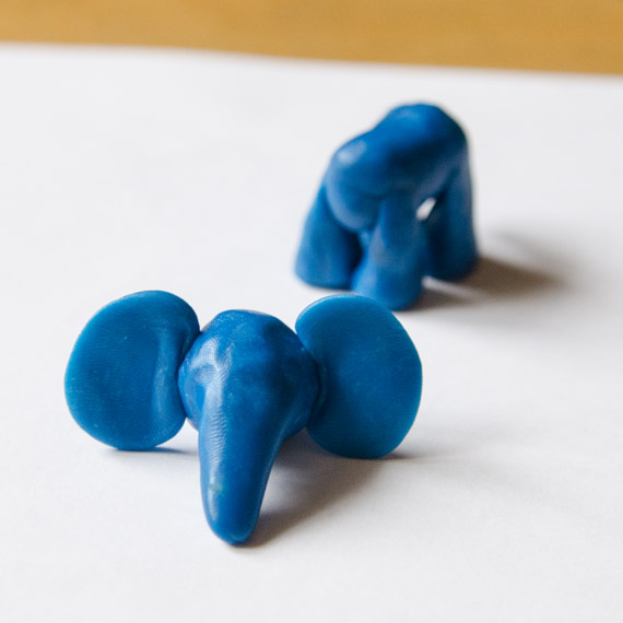 Слепите тонкие уши слонёнка и прикрепите их к голове