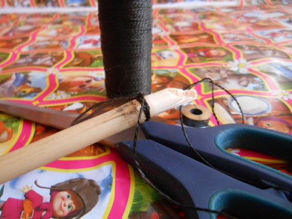 Отрежьте палку нужной длины и привяжите к ней нитку