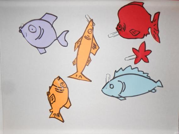 Вырежьте рыбок и прикрепите ко ртам скрепки