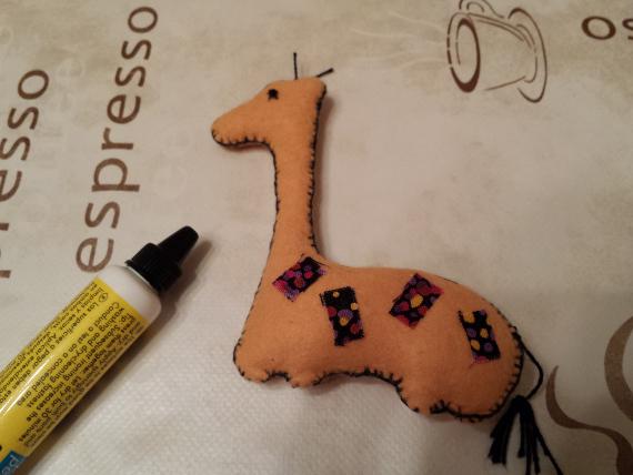 Сделайте глаза и пятна на боках жирафа