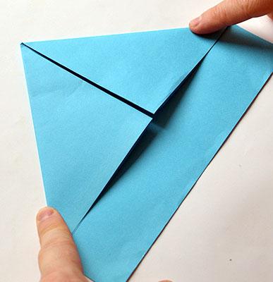 Возьмите лист за верхние уголки и согните их внутрь