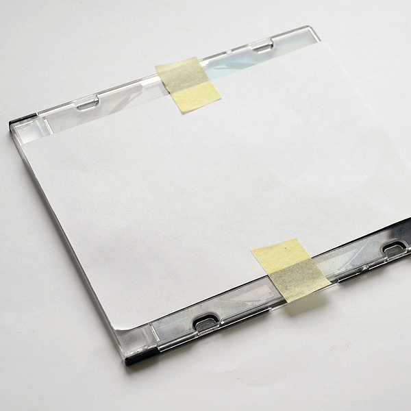 Приклейте скотчем распечатку к внешней стороне коробки от диска