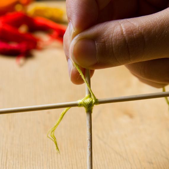 Кончик нитки, который у нас остался от первого узелка, пустите вдоль палочки и обмотайте его вместе с палочкой