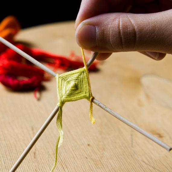 Прикрепите нитку другого цвета на любую из палочек одинарным узелком и плетите дальше