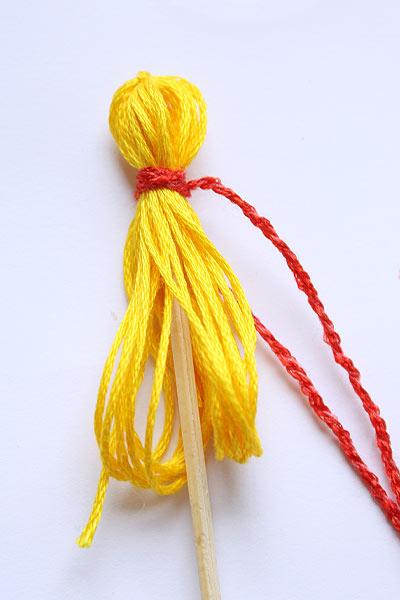 Проденьте шпажку внутрь ниток и обвяжите красной ниткой