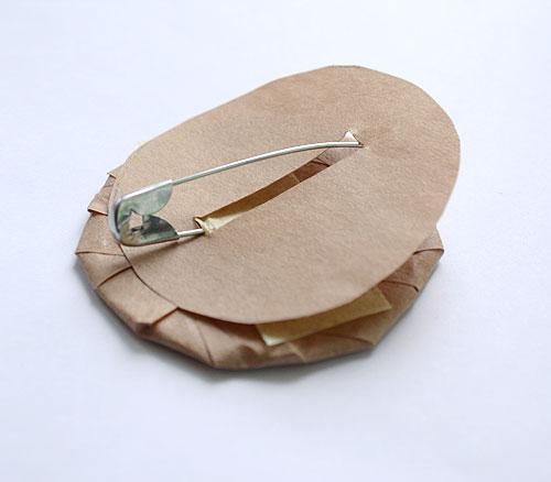 Наложите сверху кружок бумаги с прорезью для булавки и приклейте