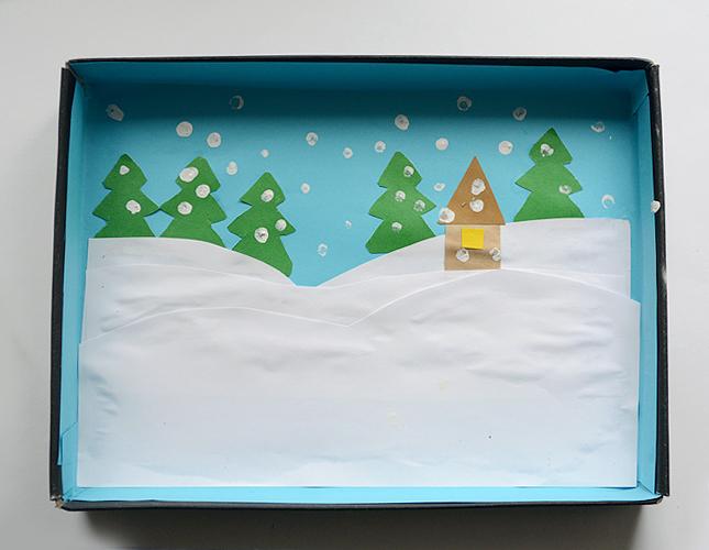 Обклейте внутреннюю часть крышки цветной бумагой, сделайте аппликацию или нарисуйте фон для диорамы