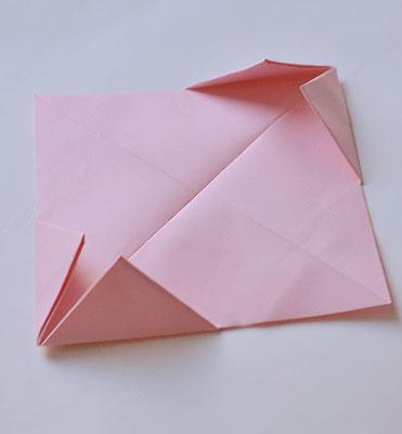 Согните образовавшиеся боковые маленькие треугольники вовнутрь